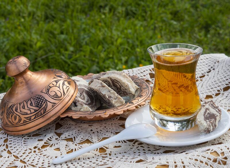 Turkish tea in a glass Cup and marble halva on a table with a handmade tablecloth and candy maker on a Sunny day. Turkish tea in a glass Cup  and marble halva on stock photo