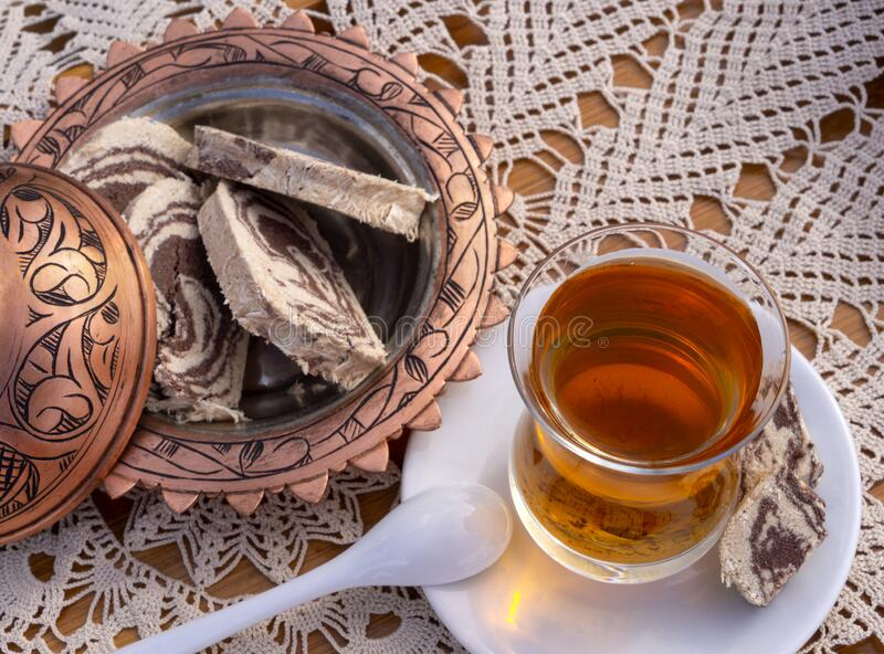 Turkish tea in a glass Cup and marble halva on a table with a handmade tablecloth and candy maker on a Sunny day. Turkish tea in a glass Cup  and marble halva on royalty free stock image