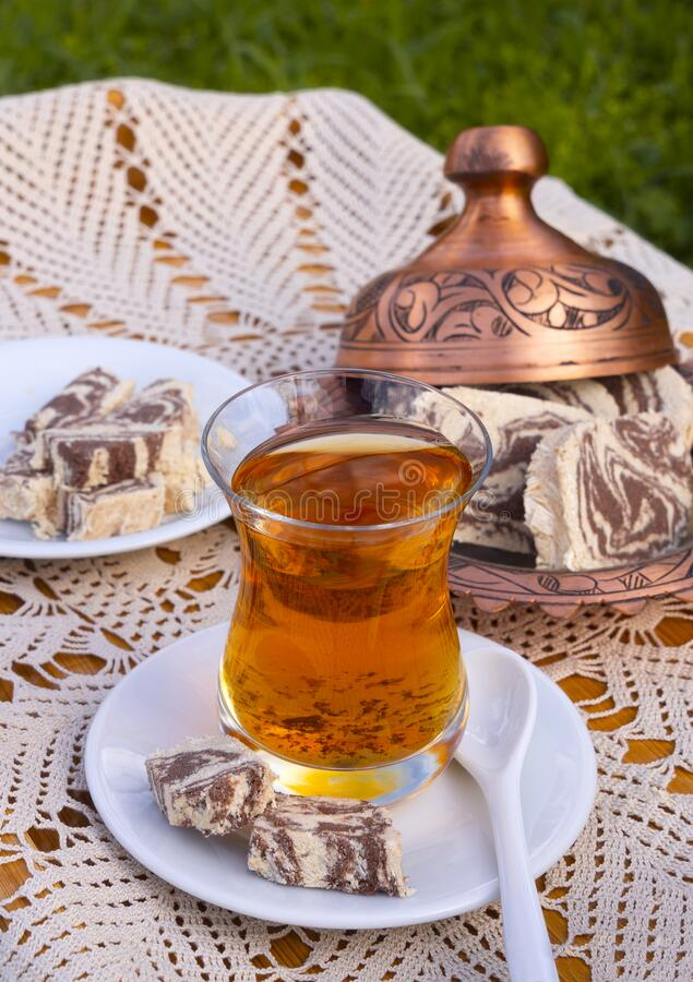 Turkish tea in a glass Cup and marble halva on a table with a handmade tablecloth and candy maker on a Sunny day. Turkish tea in a glass Cup  and marble halva on royalty free stock images