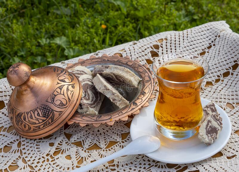 Turkish tea in a glass Cup and marble halva on a table with a handmade tablecloth and candy maker on a Sunny day. Turkish tea in a glass Cup  and marble halva on royalty free stock photo