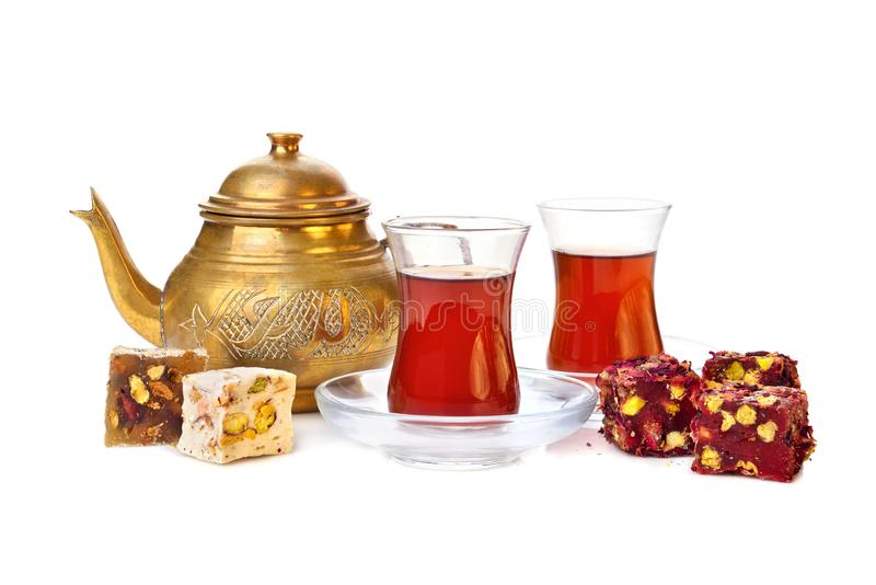 Turkish tea with rahat lokum. Traditional turkish delight rahat lokum with two glasses of tea and teapot on a white background royalty free stock image