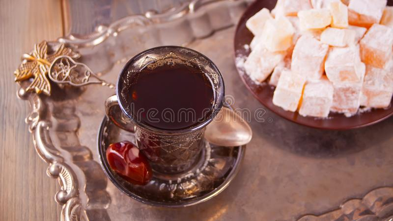 Turkish tea in traditional glass cups on the metal tray. Turkish tea in traditional glass cups, date fruits and sweets on the metal tray. Oriental royalty free stock photo