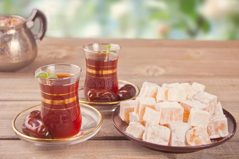 Turkish tea in traditional glass cups on the wooden table. Turkish tea in traditional glass cups, date fruits and sweets on the wooden table. Oriental stock images