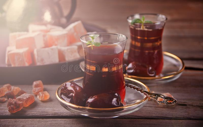 Turkish tea in traditional glass cups on the wooden table. Turkish tea in traditional glass cups, date fruits and sweets on the wooden table. Oriental stock image