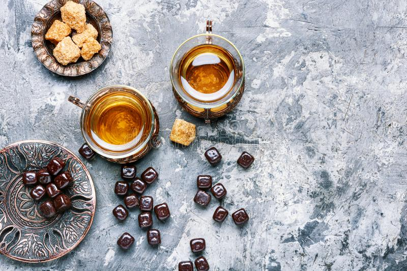 Turkish tea in traditional glass. Eastern tea concept.Eastern tea in traditional glass with chocolate candy royalty free stock photo