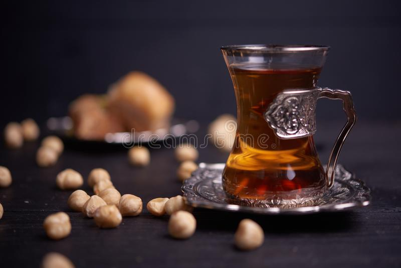 Turkish tea in traditional glasses with nuts and baklava on wooden background royalty free stock image