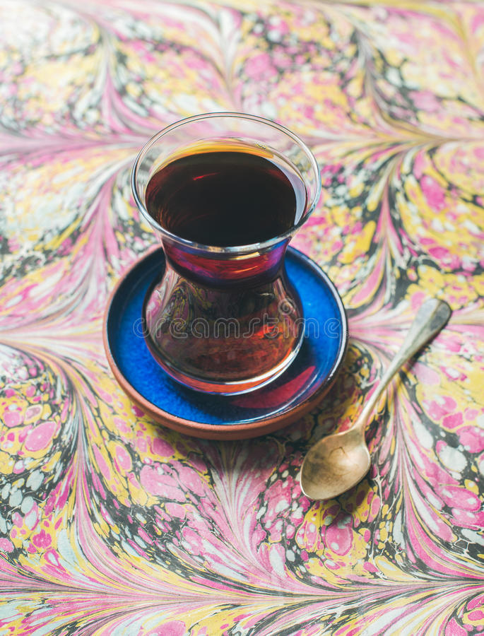 Turkish tea in traditional oriental tulip glass over colorful background. Turkish tea in traditional oriental tulip glass over ebru painted colorful paper stock photography