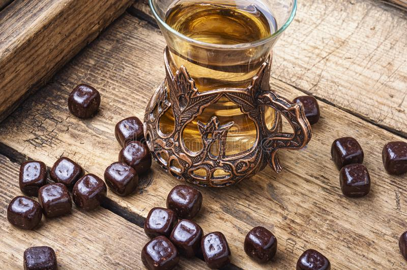 Turkish tea on wooden table. Eastern tea concept.Eastern tea in traditional glass with chocolate candy royalty free stock image