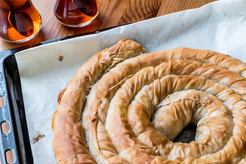 Turkish Tepsi Boregi / Round Borek in tray with tea. Round Borek in tray / Greek Cheese pie on wooden surface stock photography
