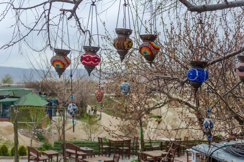 Turkish traditional colored glass craft lights on the branches of a tree close-up. Early spring, preparation for the tourist. Traditional Turkish multicolored royalty free stock photos