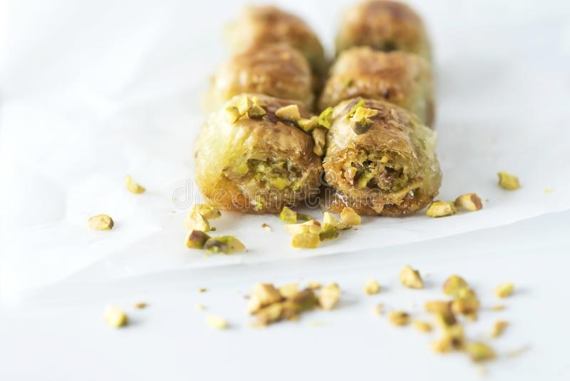 Turkish traditional dessert Baklava with pistachios on a white baking paper, isolated, close up royalty free stock photography