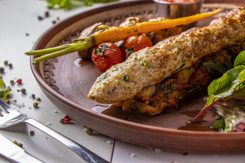 Turkish Traditional mix kebab with baked vegetables, mushrooms and tomato sauce, horizontal orientation. Turkish Traditional mix kebab with baked vegetables royalty free stock photos