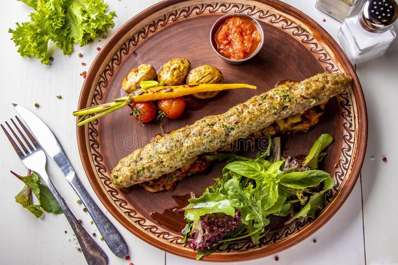 Turkish Traditional mix kebab with baked vegetables, mushrooms and tomato sauce, top view, horizontal orientation. Turkish Traditional mix kebab with baked royalty free stock images