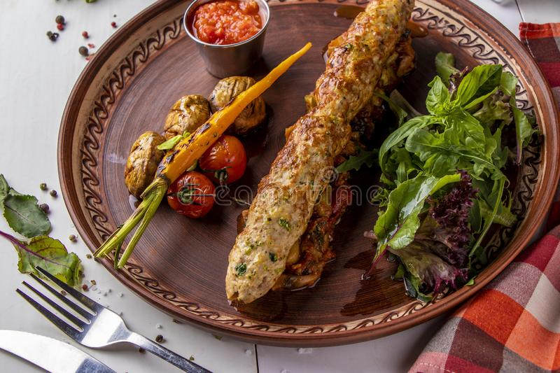 Turkish Traditional mix kebab with baked vegetables, mushrooms and tomato sauce, top view, horizontal orientation. Turkish Traditional mix kebab with baked royalty free stock image
