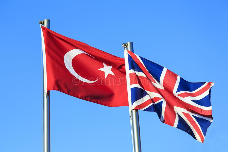 Turkish and UK flags on blue sky background. Turkish and United Kingdom UK flags on blue sky background royalty free stock photography