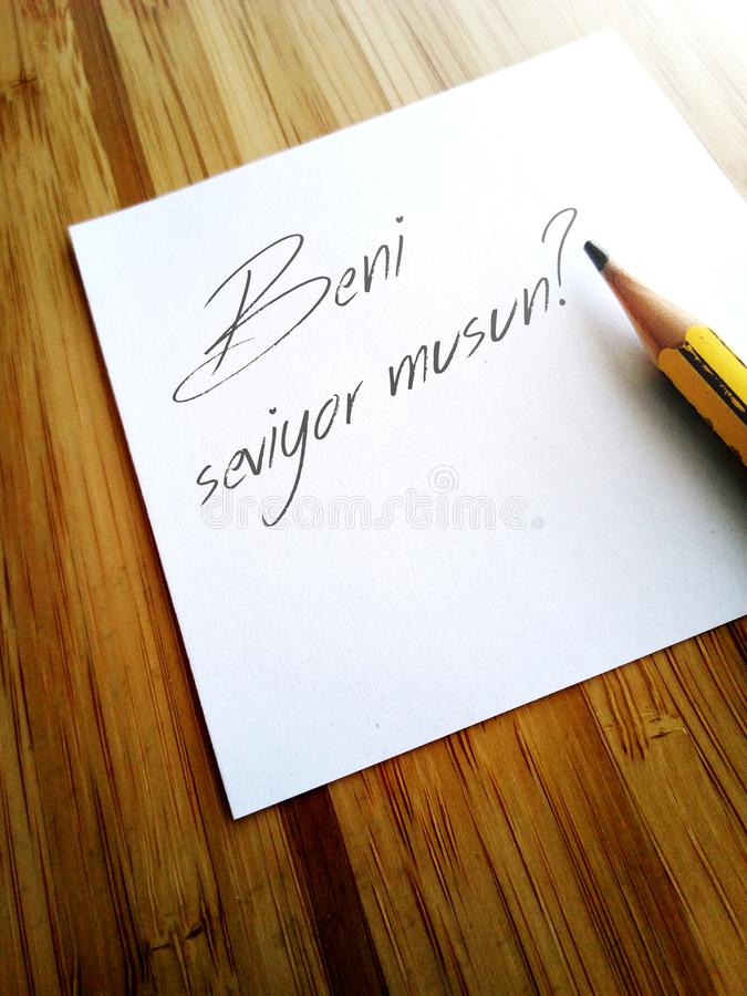 Beni seviyor musun? - Do you love me? - Turkish write on white note stock photo