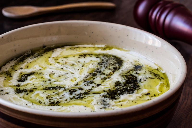 Turkish Yayla or Yogurt Soup with mint sauce Tzatziki. On a wooden surface royalty free stock images
