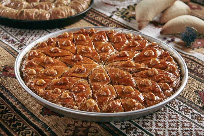Turkisk Baklava i ett runt metallmagasin på traditionell bordduk för tappning royaltyfri bild