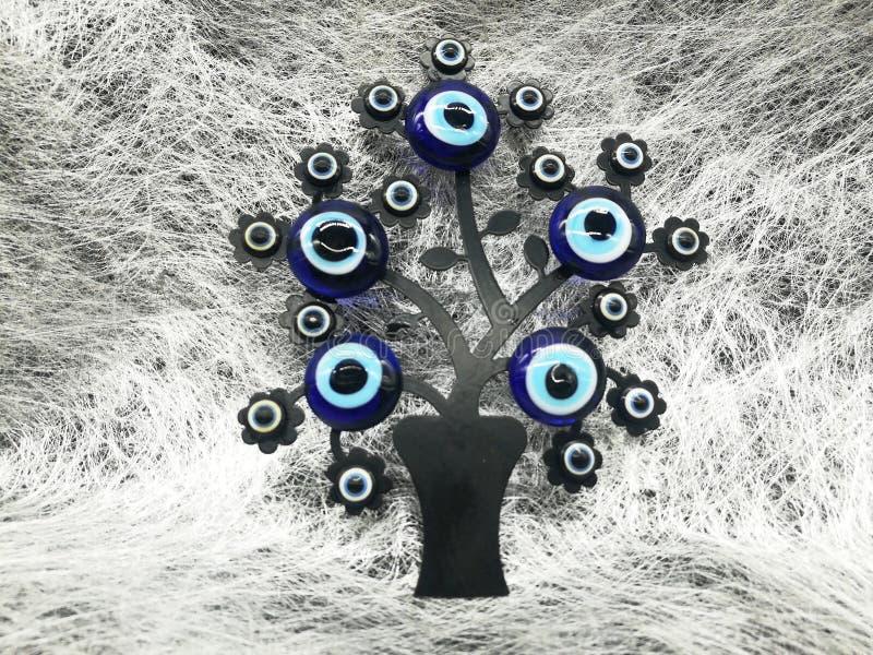 Turkisk dekorativ amulett för skydd Magiskt symbol Nazar berlock som av avvärjer det onda ögat, på filialerna av ett träd grunge royaltyfria bilder