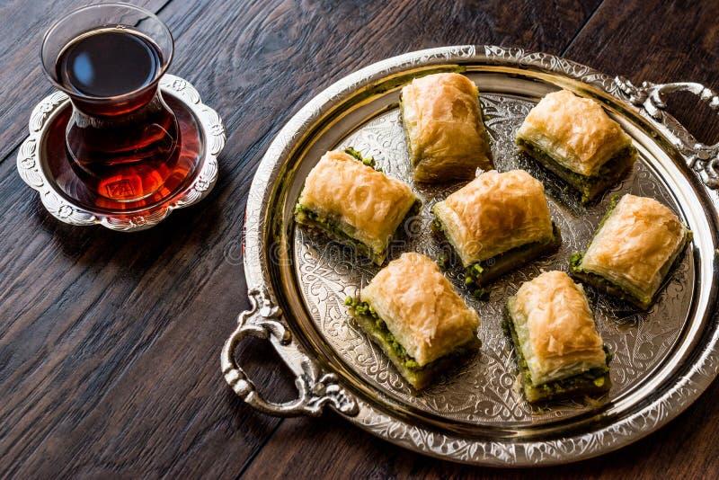 Turkisk efterrättBaklava med te på silvermagasinet royaltyfri bild