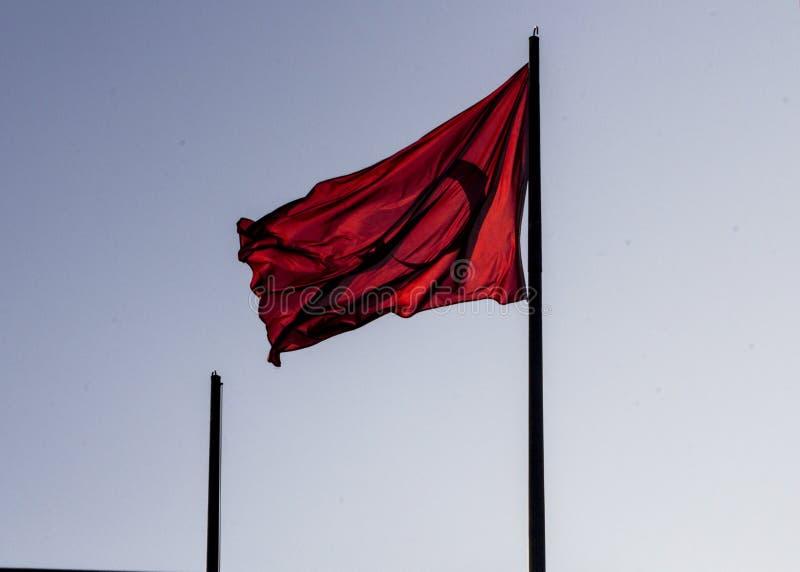 Turkisk flagga som strömmar i vind och tvättar med aftonsolen på en pol royaltyfria foton