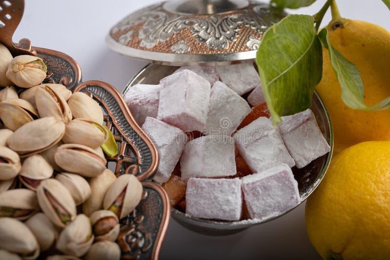 Turkisk fröjd i järn oftare med en prydnad Pistascher i en kopparbunke med modeller och prydnader och två citroner royaltyfria foton