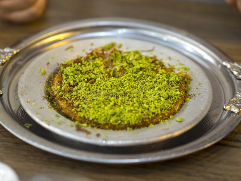 Turkisk kunefeefterrätt i special portionmaträtt med den gröna pistaschen fotografering för bildbyråer