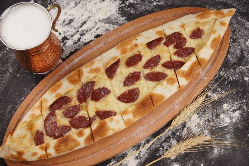 Turkisk pizza i form av ett fartyg kallas en pied överträffad bakad sudzhuk, bredvid en nationell drink av mjölkar ayran arkivbild