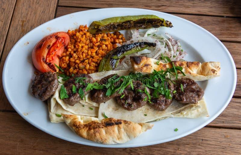 Turkiska kofteköttbollar med bulgursädesslag och bröd arkivbild