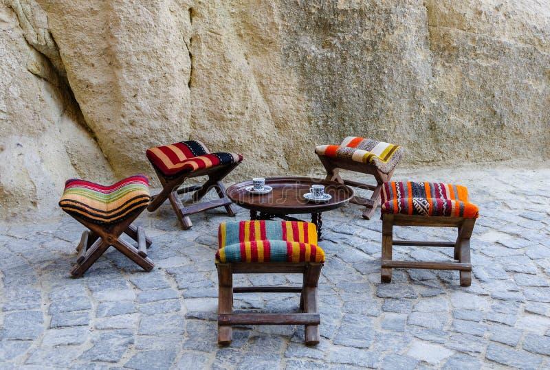 Turkiskt gatakafé i museum Goreme för öppen luft Trätraditionella tabell och stolar på gatan Två koppar av turkiskt kaffe arkivbilder