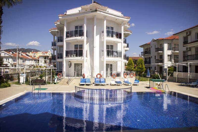 Turkiskt hotell med en simbassäng framtill av det och en bakgrund för blå himmel royaltyfri foto