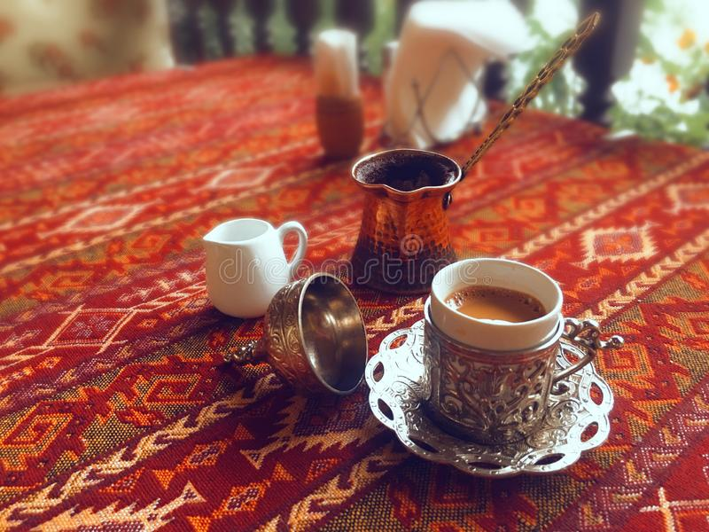 Turkiskt kaffe i metallkopp med prydnader på röd bakgrund royaltyfria bilder
