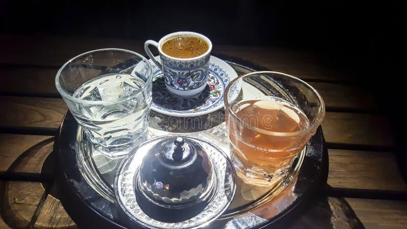 Turkiskt kaffe i traditionell kopp med exponeringsglas av vatten arkivfoton
