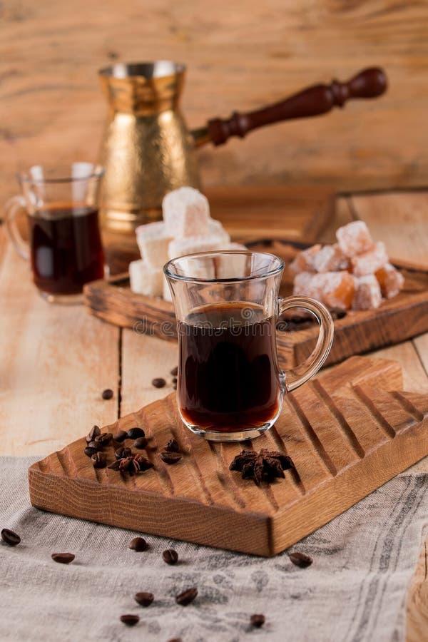 Turkiskt kaffe in i traditionell präglad metallturk kaffekorn, turk, kaffekvarn på en träbakgrund royaltyfri bild