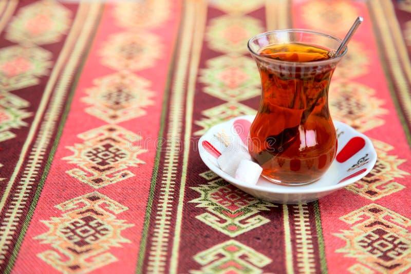 Turkiskt te i traditionell glass kopp på handgjord arabisk tableclo royaltyfri foto