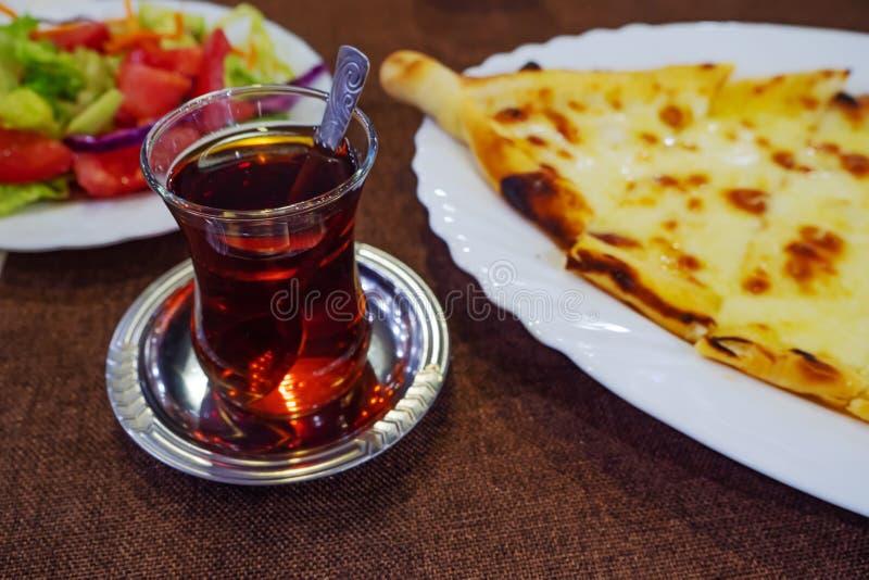 Turkiskt te i traditionellt exponeringsglas och startknapp på tabellen arkivfoto