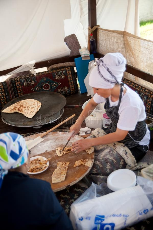 Woman cooking cakes gozleme. Hotel in Turkey. Turkler, Turkey - July 27, 2018: Senza hotel tent. Turkish woman makes a traditional national dish - a baked flat royalty free stock image