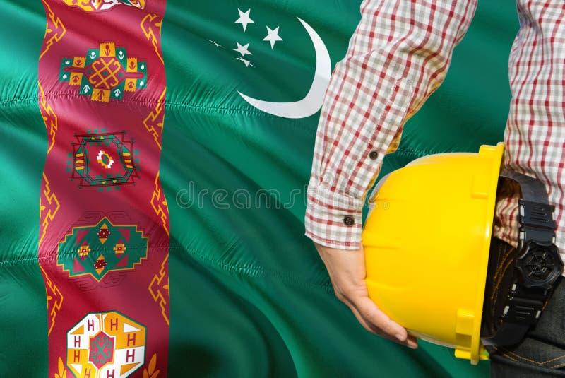 Turkmeński inżynier trzyma żółtego zbawczego hełm z machać Turkmenistan chorągwianego tło Budowy i budynku poj?cie zdjęcia stock