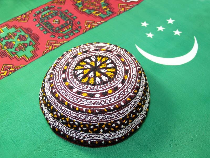 The Turkmen skullcap lies on a flag of Turkmenistan stock photos