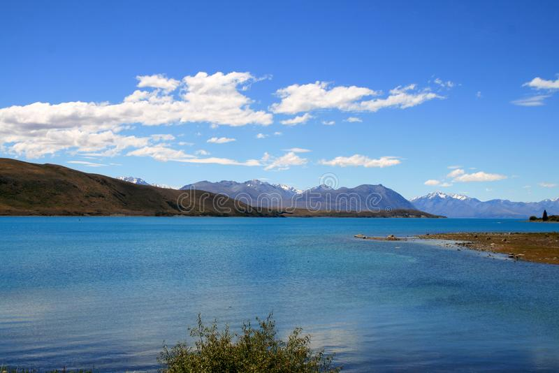 Turkoois blauw die meer Tekapo door heuvels van Zuidelijke Alpen in rug wordt omringd stock fotografie