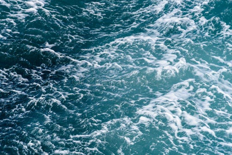 Turkoois en blauw oceaanwater met een sleep van bellen en golven als aardachtergrond stock afbeelding
