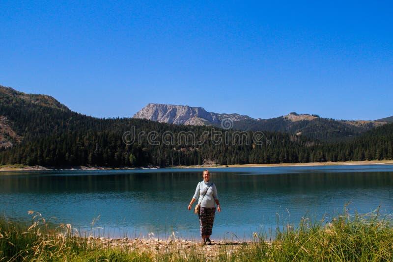 Turkoois water van het meer, het pijnboombos en de bergen Overweldigende achtergrond met zich het meisje van de aardtoerist het v stock fotografie