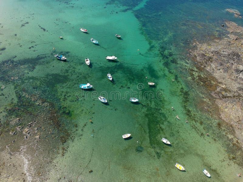 Turkoois zeewater en kleine vissersboten in Zuidenkust van Guernsey-eiland royalty-vrije stock afbeelding