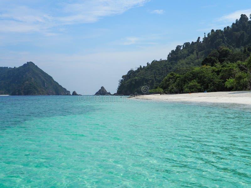 Turkoois zeewater en wit zandstrand met blauwe hemel stock foto's