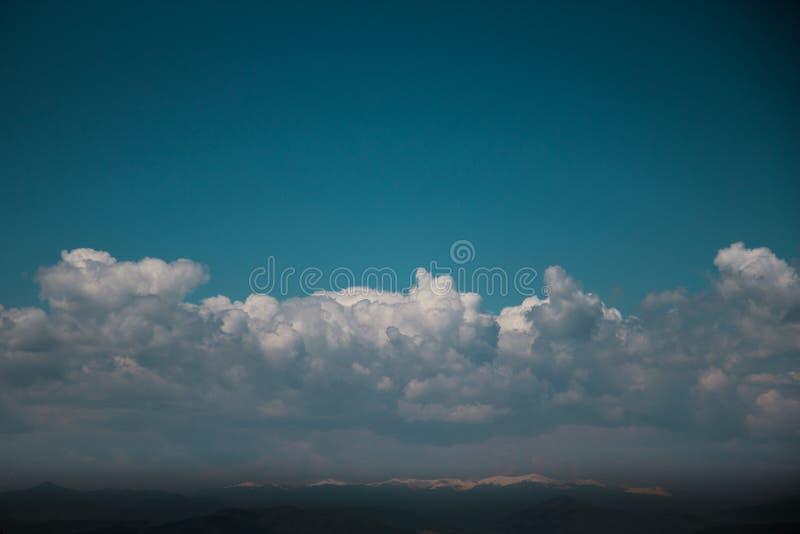 Turkooise Blauwe Hemel met Wolken over Bergbovenkanten stock foto