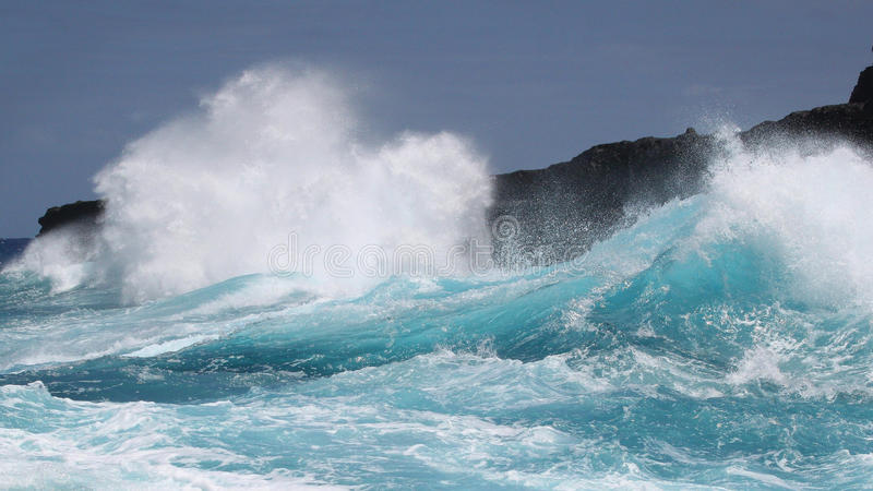 Turkooise golven die tegen lavaklippen verpletteren royalty-vrije stock afbeeldingen