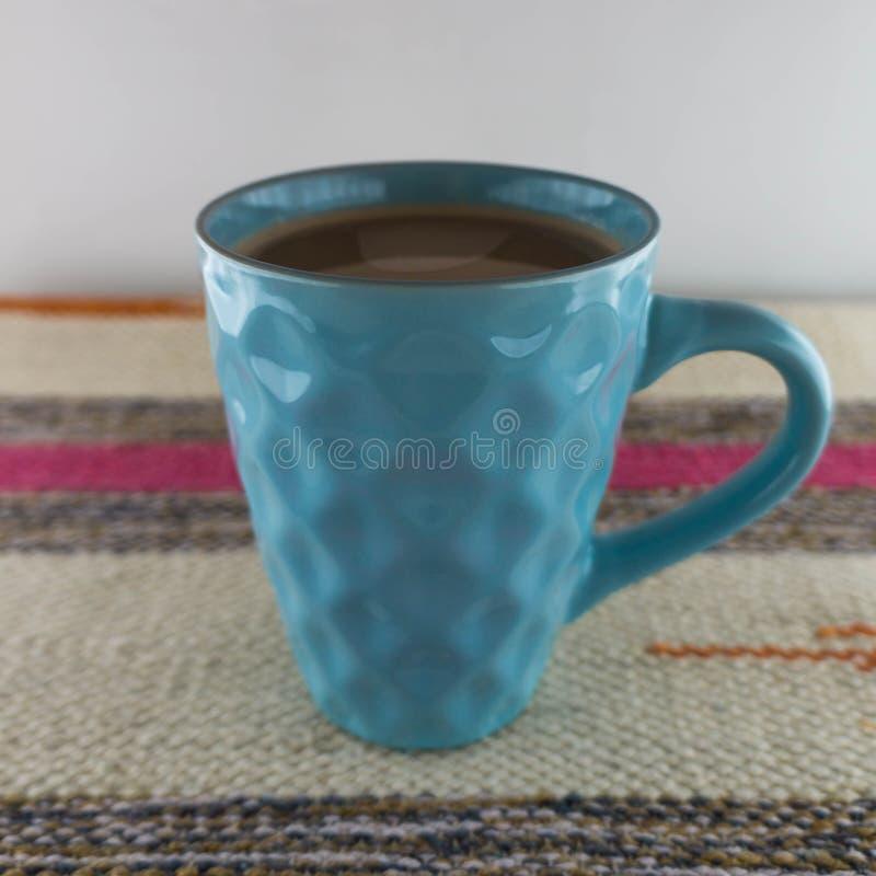 Turkooise Kop van koffie tegen de gestreepte gevlechte deken royalty-vrije stock afbeelding