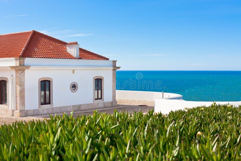 Turkooise overzees, blauwe hemel en wit huis in Portugal stock fotografie