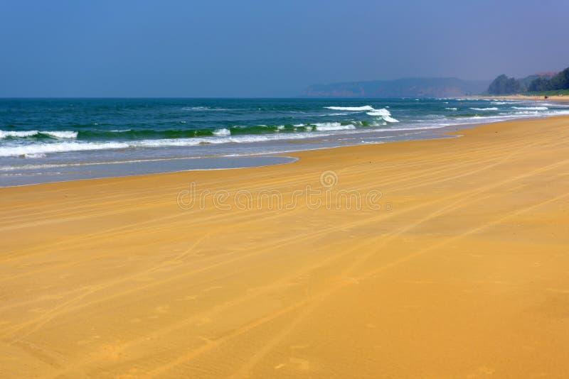 Turkooise overzees en geel zand tegen blauwe hemel en groene heuvels in de afstand Weergeven van lange fietssporen op het strand  royalty-vrije stock afbeelding