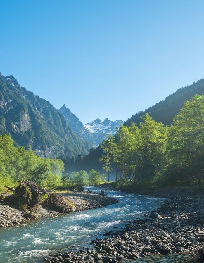 Turkooise rivier die door de olympische bergen op duidelijk winden stock foto's